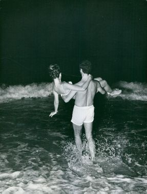 A man carries a woman while going towards the beach water.  - Sep 1966