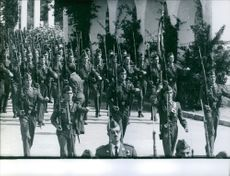 Juan Carlos de Borbón- of Spain with soldiers marching.