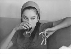 Geraldine Chaplin holding glass in front of her face.