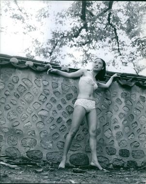 A photo of woman standing beside a wall and posing in bikini looking up.
