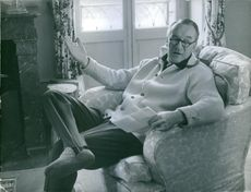 George Henry Sanders sitting on couch.