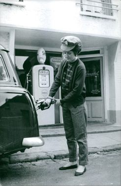 Alice Dona pumping gas in to her car at a gas station.