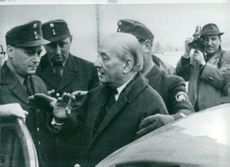 Georges Bidault in talks with Bavarian policemen after prosecution hearing