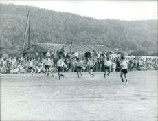 Men playing soccer in ground and people watching.
