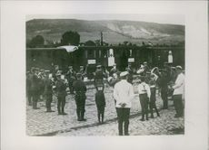 Soldiers playing musical instruments, other people standing there looking at them during first world war.