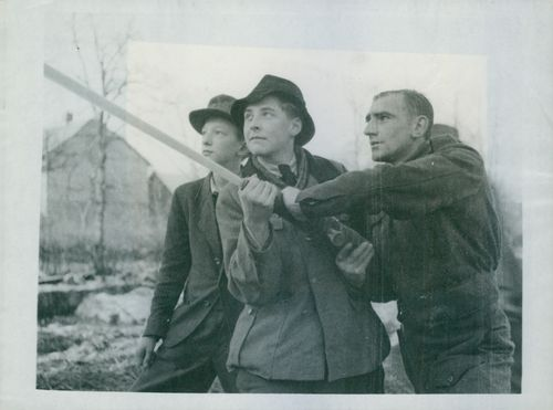 Two young Germans help British Tommy use a hose on the blazing farm.