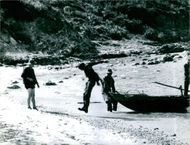 People at beach, soldiers trying to pull the boat.