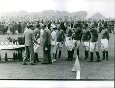 Prince Philip with his wife Elizabeth II distributing trophy to players.