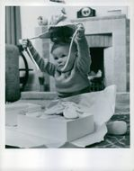 Young Douglas opening his present and trying on the hat.