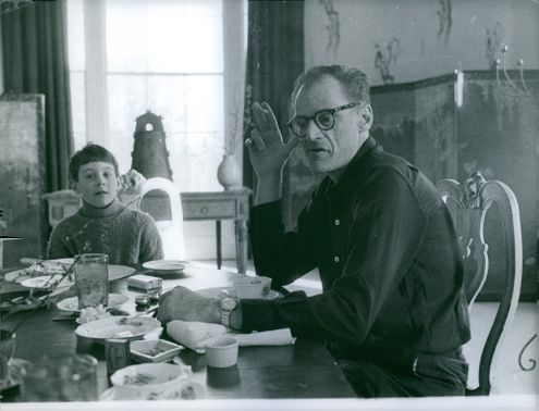 Arthur Miller smoking a cigarette while having a meal with his son. 1960,