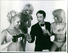 A man being served with a bottle of champagne by three women with body paint.