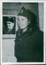 Twenty-year-old Yugoslav Partisan standing beside the picture of her leader, General Tito.