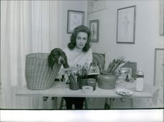A woman with a dog in a basket placed on a table. December 18, 1962.