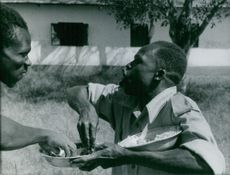 Two men eating together in Kongo.