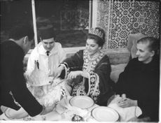Wife of Prince Moulay Abdallah of Morocco Lamia Solh cutting a cake with smiling face