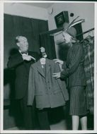 Maurice Auguste Chevalier holding coat and showing to a woman.