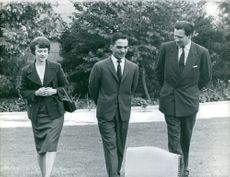 King Hussein of Jordan walking with Princess Muna al-Hussein and unknown man. 1961.