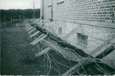 Barb wires on a wood fencing securing a building when polished officers have been prisoned in Germany.  Taken - Circa 1939
