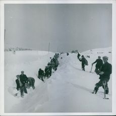Norwegian battle - long column of people helping in shoveling the snow.