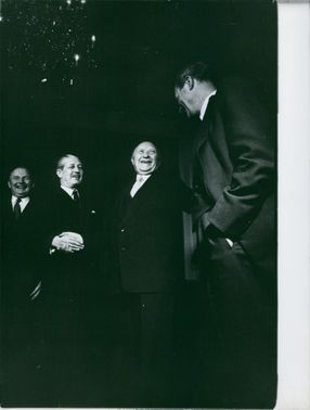 Konrad Adenauer laughs as he shakes hand with a man on his side while others laugh with him.