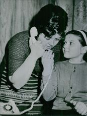 Woman taking on the telephone while her daughter wants to talk.