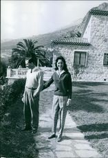 Man and woman standing together in a garden and smiling.