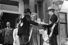Two men showing the cake to Queen Juliana, her husband Prince Bernhard of Lippe-Biesterfeld in the background.  - 1969