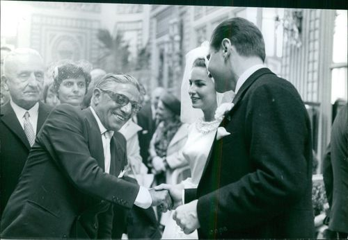 A man shaking hands to the groom and smiling, 1963.