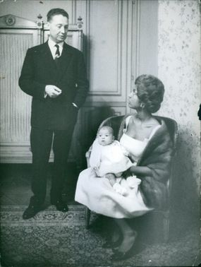 A man talking to the woman sitting on a chair and carrying her young child.