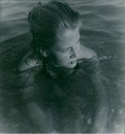 Woman batthing in the water, looking away.