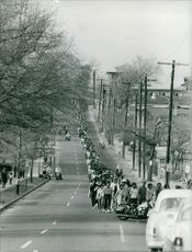A large queue of people on road.