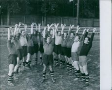 Football team raising hand before start the game. 1943