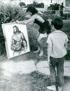 Gipsy Boots holding a painting in the yard.Photo taken on 1967