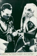 From the wedding between Rainier III of Monaco and Grace Kelly. Prince Rainier puts the ring on the bride's finger
