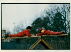 Children lying on front on seesaw.