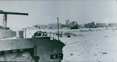 View of a damaged military tank in an empty street.