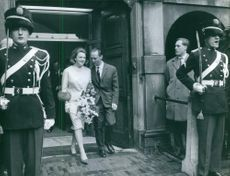 Carlos Hugo talking and smiling with his wife, Princess Irene of the Netherlands with guards guarding.