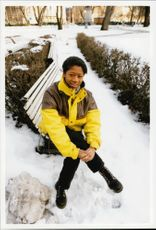 Photography on the artist Gladys del Pilar. She is sitting outdoors on a bench in the snow.