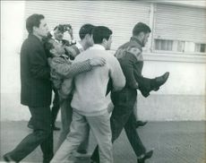 People carrying an unconscious man.