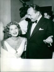 Actress Rhonda Fleming is smiling with a men in a program