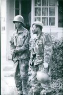 Two soldiers standing together and talking.