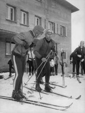 Aga Khan IV standing on skis.