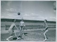 Footballers playing football on the beach.