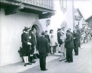 Elizabeth II with other people being welcomed by the people.