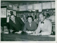 Three people as salesperson at the counter.