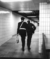 A police officer escorts a man out of a subway.