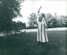 A photo of a three time Emmy Award English Actress Susan Hampshire standing in the grass in a dramatic pose.