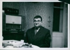 Man sitting in the room beside the dining table.