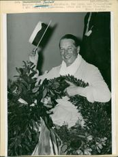 Portrait of Maurice Chevalier smiling and posing for camera.