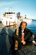 "Peter Forbes from the dance band Forbes on the quay in Vaxholm with the ship ""Skarpö"" in the background"
